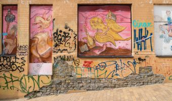 Colourful graffiti/street art on a yellow wall on Andrew's Descent in Kiev, Ukraine.