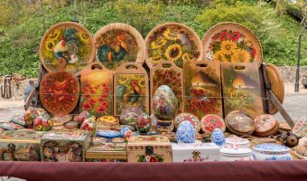 Photo of a souvenir stall with painted wooden plates, chopping boards, eggs, and boxes. Taken on Andrew's Descent in Kiev, Ukraine.