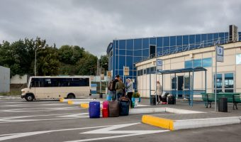 Photo of passengers waiting with suitcases at a bus stand at Vydubychi Bus Station in Kiev, Ukraine.