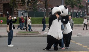 Costume characters on Khreshchatyk in Kiev, Ukraine. Posing for photos with men dressed in panda suits.