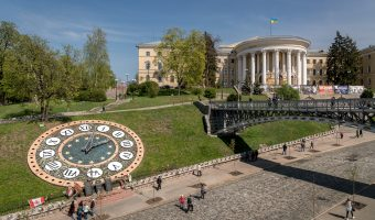Floral Clock and the October Palace on Heroyiv Nebesnoyi Sotni Alley in Kiev, next to Independence Square. Monuments to the victims of Euromaidan can be seen before the clock.