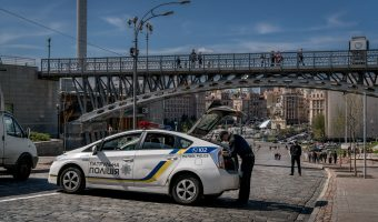 Photograph of Ukrainian police officers and a police car on Heroyiv Nebesnoyi Sotni Alley in Kiev. The bridge in the background links Independence Square to the October Palace.