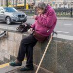 Babushka (old woman) sat on a wall and smoking. Photo taken outside Universytet Metro Station in Kiev, Ukraine.