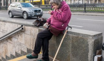 Babushka (old woman) sat on a wall and smoking. Photo taken outside Universytet Metro Station in Kiev, Ukraine.