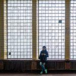 Girl standing next to the window in the vestibule of Arsenalna Metro Station in Kiev, Ukraine.